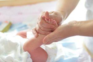 maman appliquant de la crème sur le corps du bébé