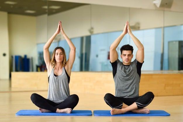 deux personnes pratiquant le yoga